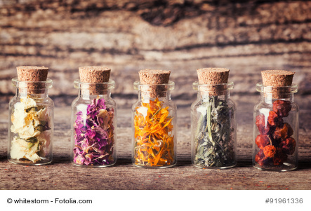Nature medicine . Herbs in bottles on wooden background.